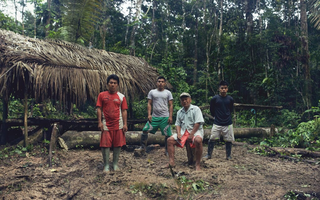Four men outside thatched-roof house in Amazonian forest.